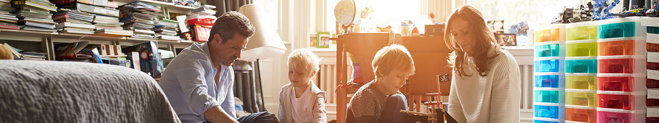 Parents with 2 sons playing with toys in their room.