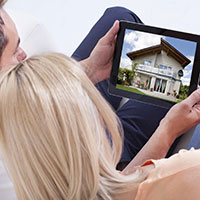 Couple looking at houses on tablet.