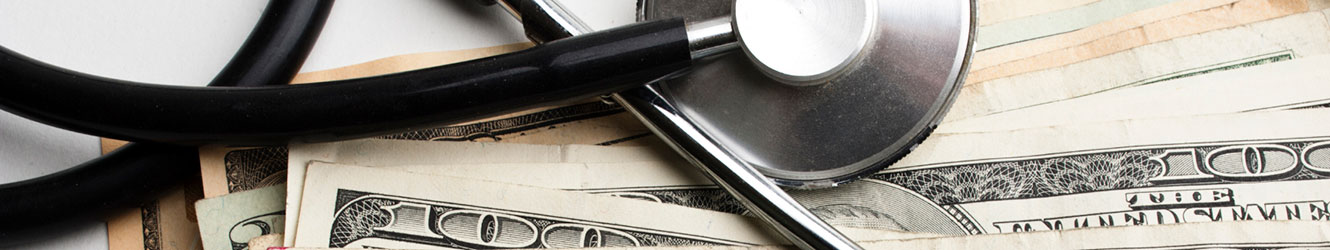 Stethoscope laying on stack of money.