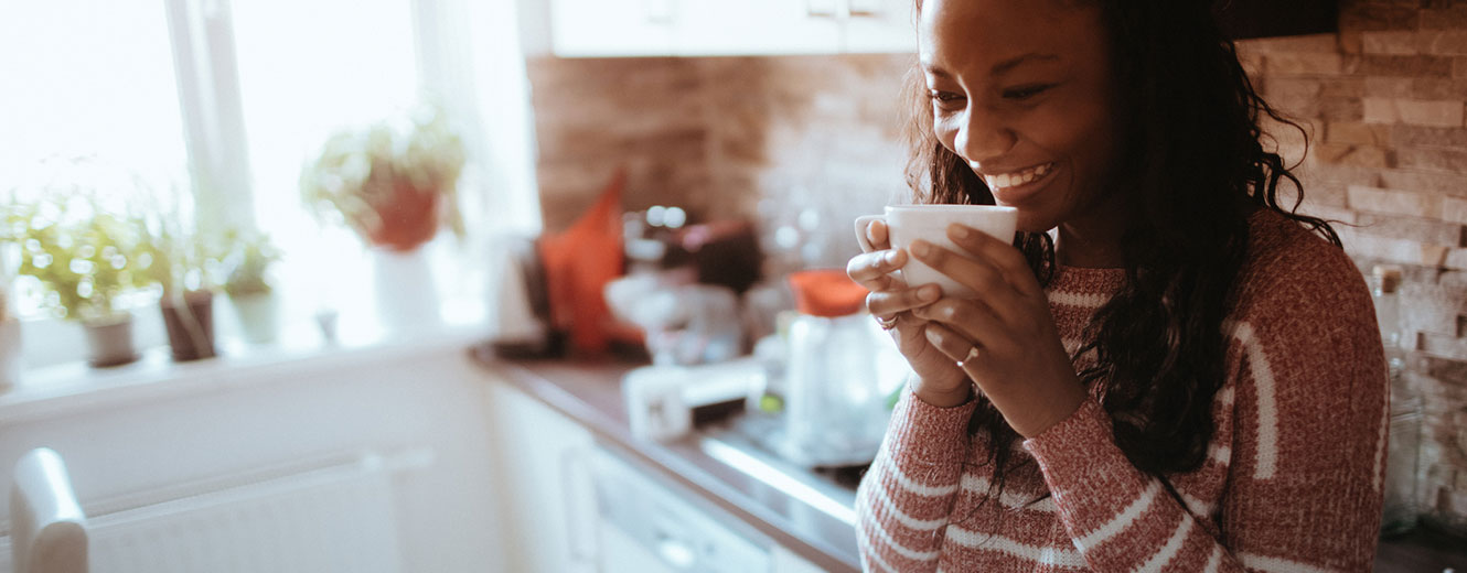 Woman in kitchen sipping coffee.